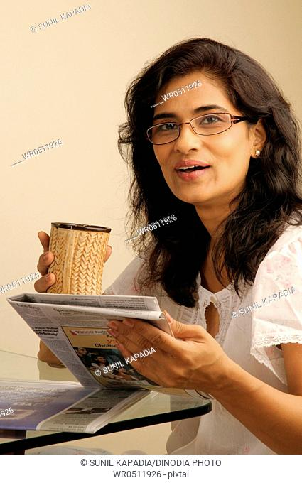 Middle age woman using spectacles holding newspaper and mug 5-June-2010 MR686U