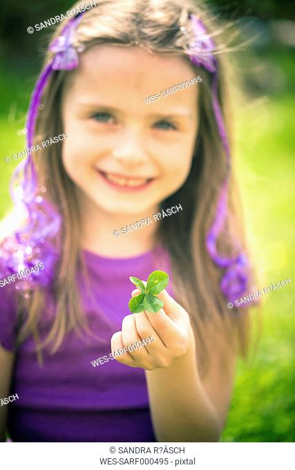 Little girl showing four leaved clover