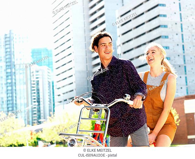 Young couple riding bicycle, Southbank, Melbourne, Australia