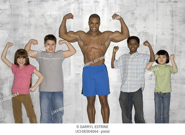 Children flexing muscles with male athlete