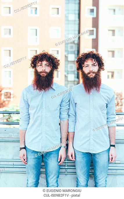 Portrait of identical male hipster twins standing on apartment roof terrace