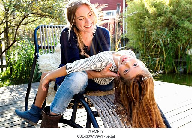 Girl sitting on mother's lap, leaning back
