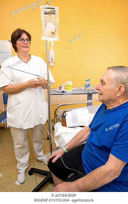 Reportage in the Internal Medecine and Geriatrics service in Saint-Philibert hospital in Lille, France. A nurse checks the flow of a patient's drip in his...