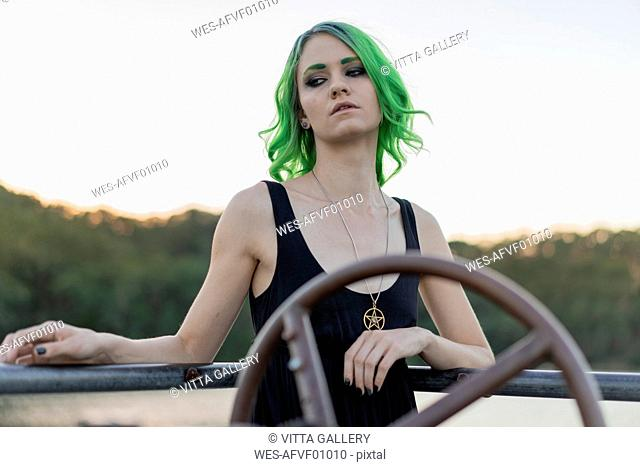 Portrait of young woman with dyed green hair and eyebrows at lake