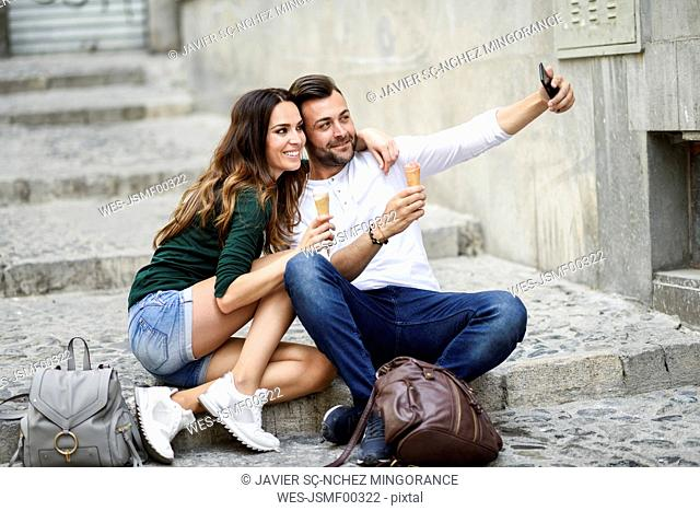 Tourist couple with ice cream cones in the city taking a selfie