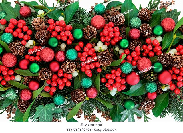 Christmas flora with red bauble decorations, holly, ivy, mistletoe, blue spruce fir and cedar cypress greenery