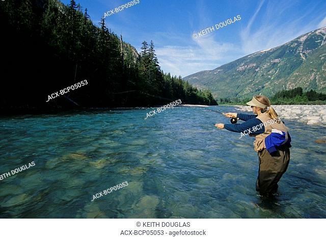 Lady flyfisher casting for steelhead, Dean river, British Columbia, Canada