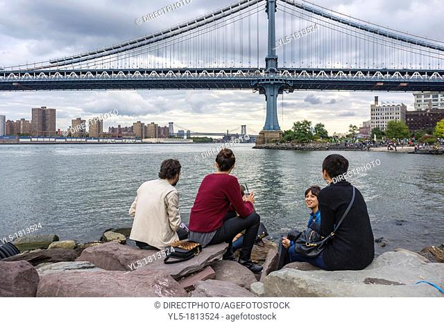 New York City, NY, USA, people Sitting, on East River Banks, Watching the Brooklyn Bridge, in DUMBO Area