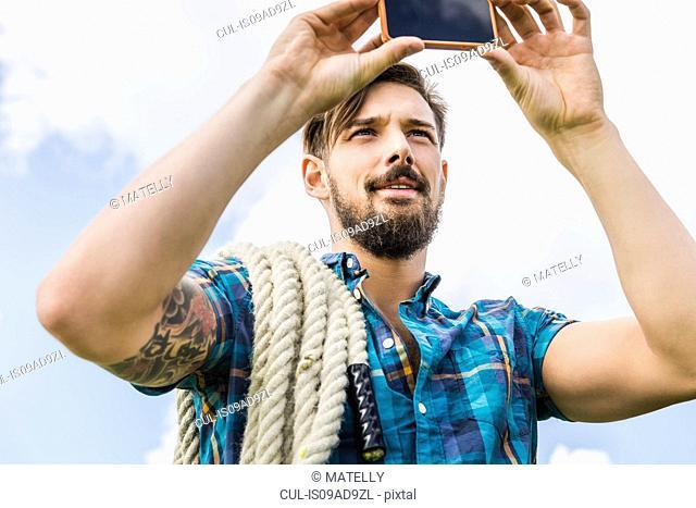 Young man using camera phone