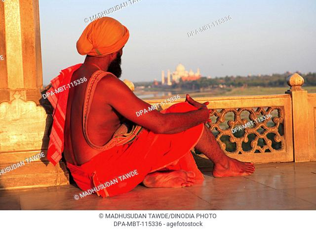 Sadhu sitting at window in Agra fort built in 16th Century by Mughal emperor on west bank of the Yamuna River ; Agra ; Uttar Pradesh ; India UNESCO World...