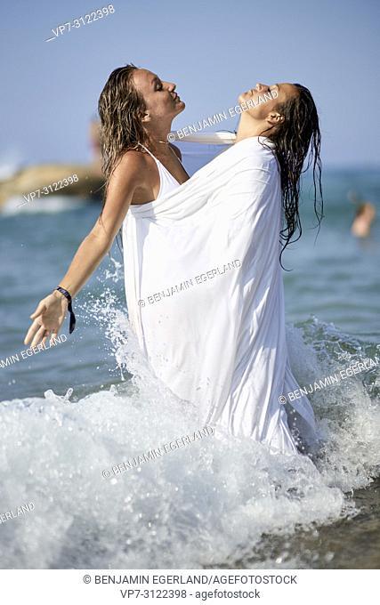 two sensual women shrouded in white blanket sheet, in sea, best friends, friendship goals, holidays, adventure, water, splashes