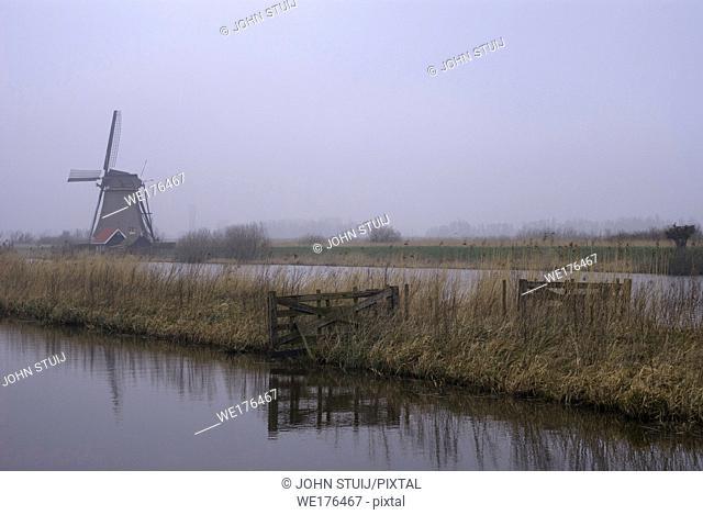 Windmill in a misty landscape at the Dutch Unesco heritage site Kinderdijk