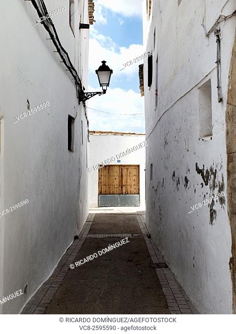Lighted door and dark street at the historic downtown in Requena, Valencia, Spain