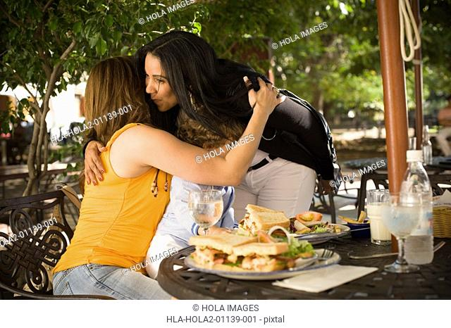 Mid adult woman hugging and kissing her friend