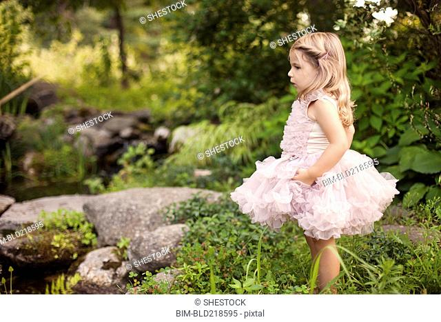 Girl in frilly dress exploring creek