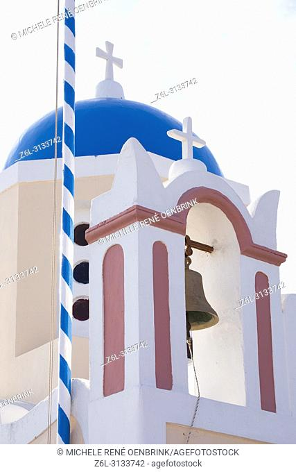 Blue domed Greek Orthodox church with bell in Oia, Santorini Greece