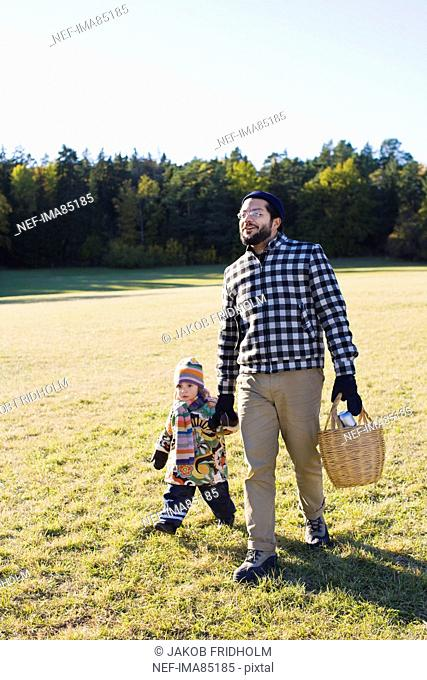 Father and daughter walking through park