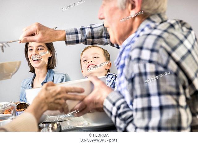 Senior man serving spaghetti to family at table