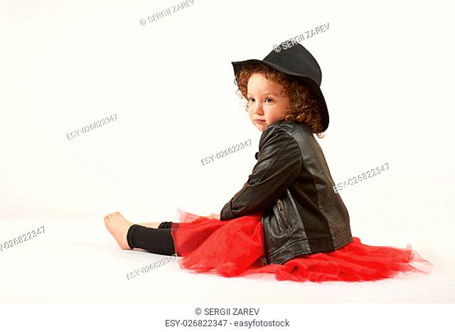 Little girl with black hat sitting and thinking