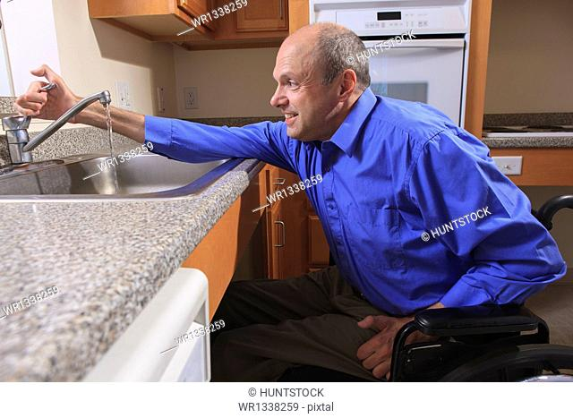 Man with Friedreich's Ataxia and deformed hands using his faucet in the kitchen