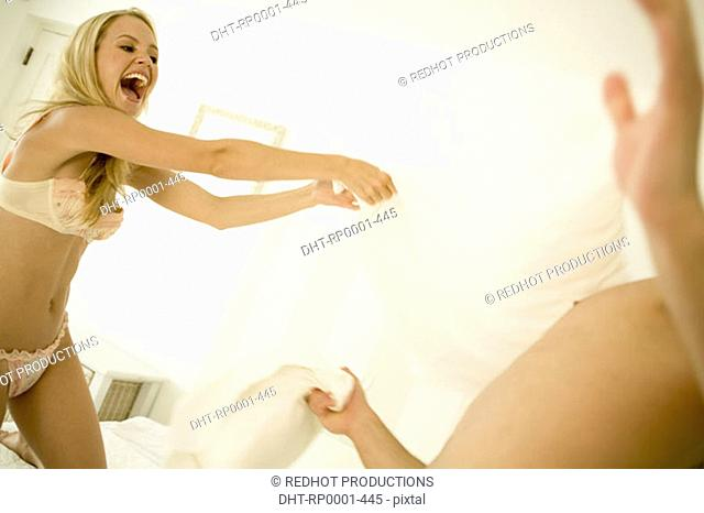 Couple in bedroom having pillow fight