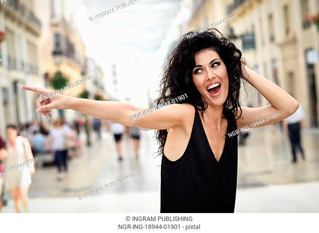 Brunette funny woman wearing casual clothes pointing with her finger in the street. Young girl with curly hairstyle standing in urban background