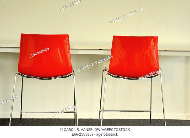 two red chairs by table against a white wall