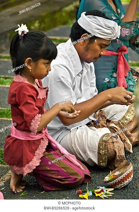 Father and daughter pray at PURA TAMAN SARASWATI during the GALUNGAN FESTIVAL , Indonesia, Bali, Ubud