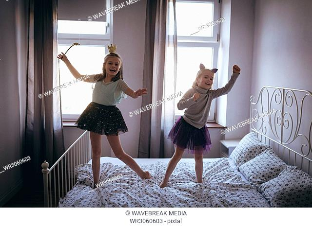 Girls in costume dancing on bed
