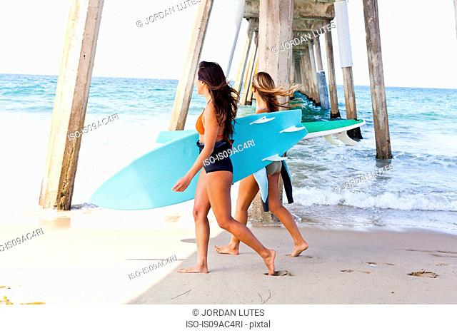 Female friends on beach with surf boards, Hermosa Beach, California, USA