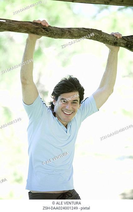 Man holding onto branch, smiling at camera