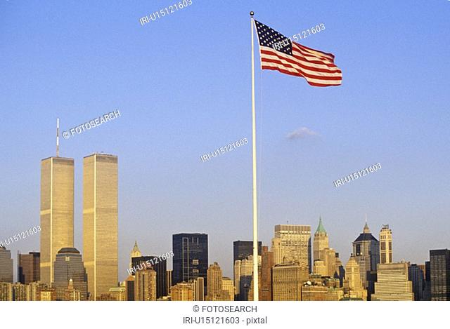 American Flag flying over skyline of New York City from New York Harbor