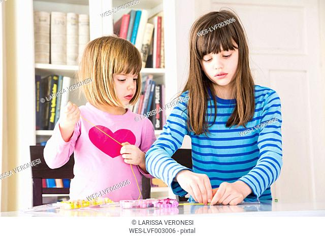 Two girls stringing pearls