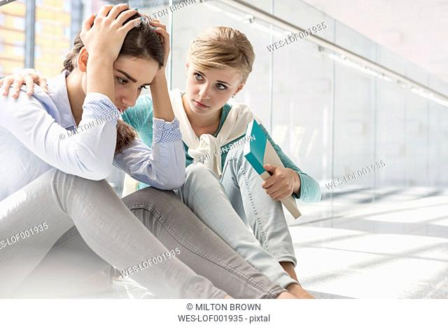 Student consoling despaired friend on hallway of university library