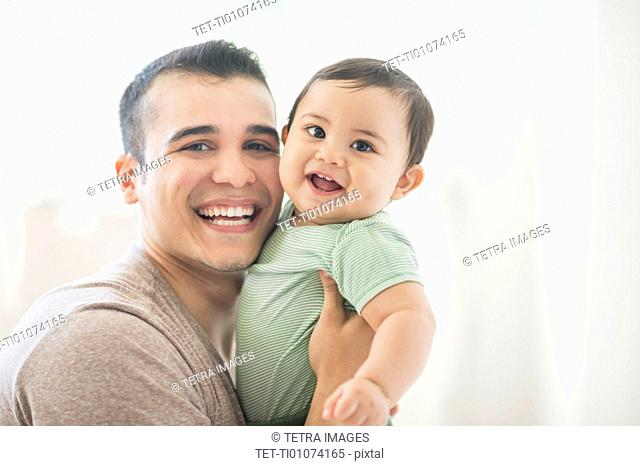 Father holding his son (6-11 months)
