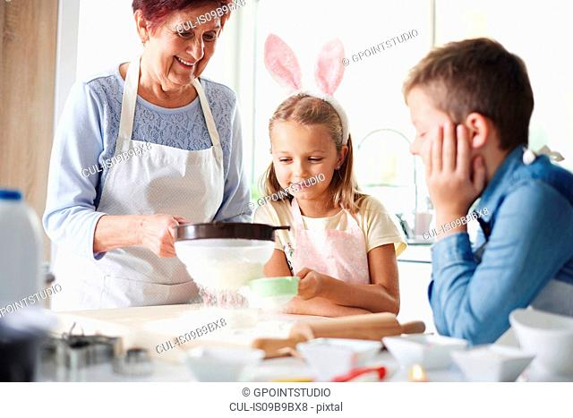 Girl and grandmother sifting flour for easter bake at kitchen counter