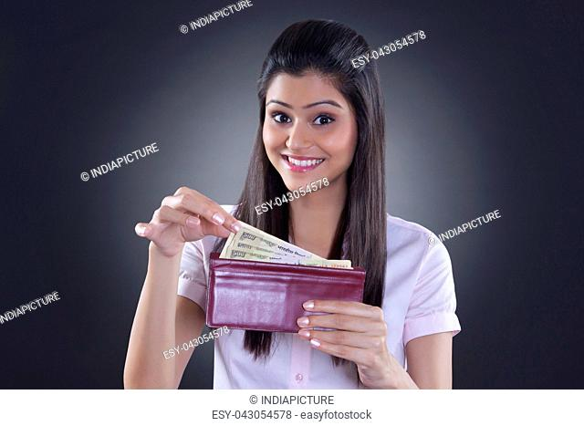 Portrait of businesswoman taking currency from wallet