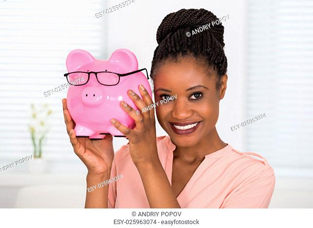 Close-up Of Smiling Young African Woman Holding Piggybank