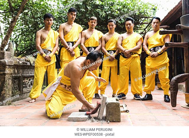 Vietnam, Hanoi, men exercising kung fu, man slabs flagstone