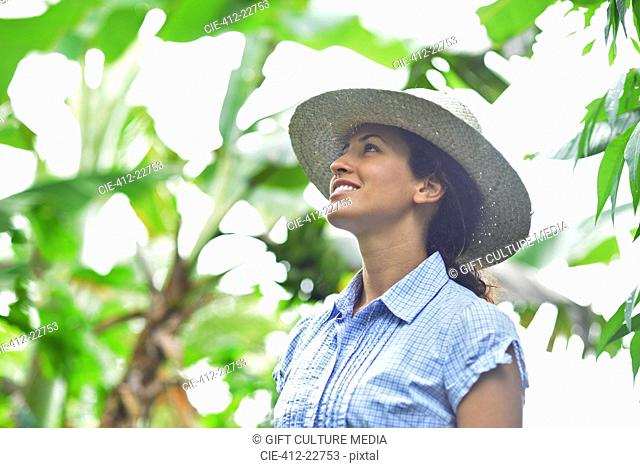 Smiling woman wearing straw hat looking at plants in sunny garden