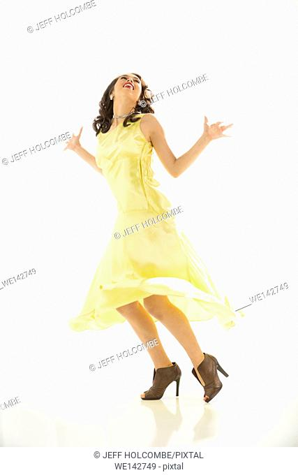Happy young woman in vintage yellow dress, dancing with jazzy hands, full length in brown heels