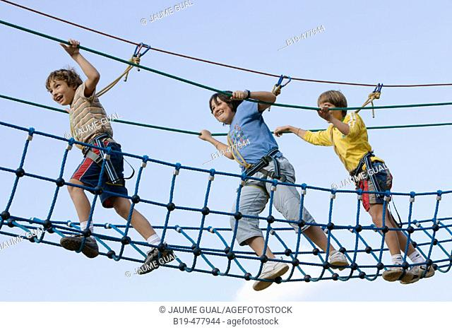 Boys crossing rope bridge in camp