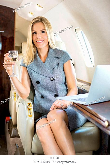 Portrait of happy businesswoman holding wineglass in private jet