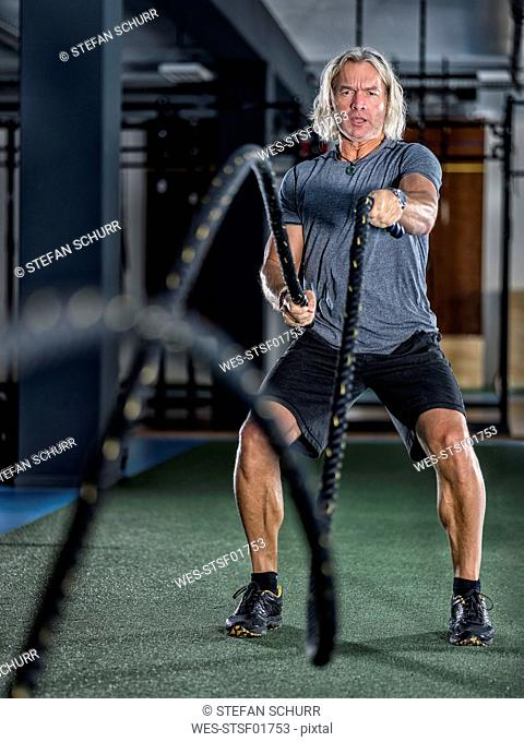 Athletic mature man exercising with battle ropes at gym