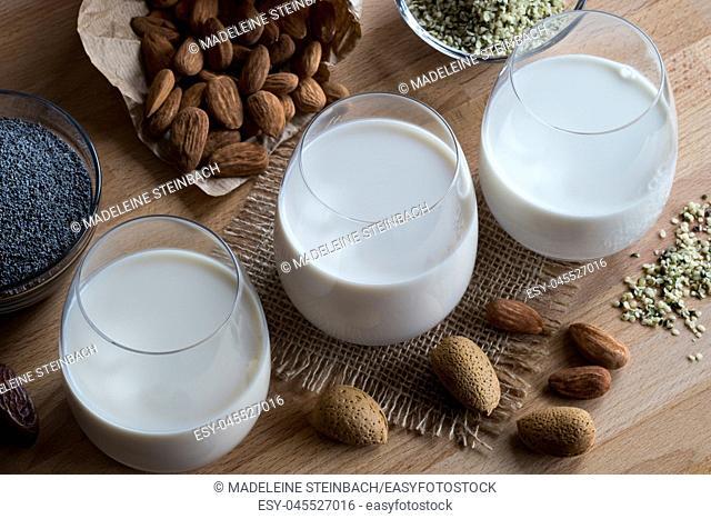 Three glasses of vegan plant milk - almond milk, poppy seed milk and hemp seed milk, with shelled and unshelled almonds, poppy seeds and hemp seeds on a wooden...