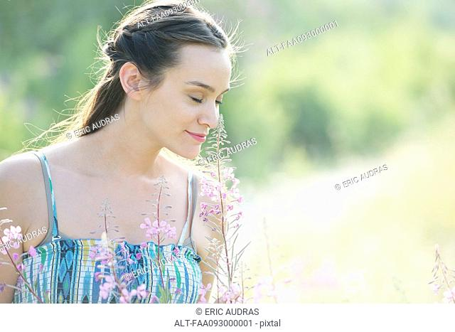 Mid-adult woman enjoying fragrence of wildlowers