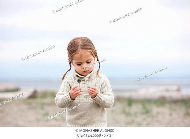 Curious girl examining pebbles on beach