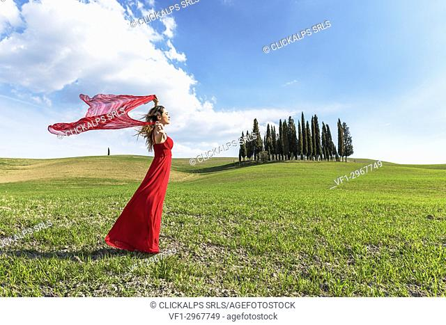 San Quirico d'Orcia, Orcia valley, Siena, Tuscany, Italy. A young woman in red dress relaxing in a wheat field near the cypresses of Orcia valley
