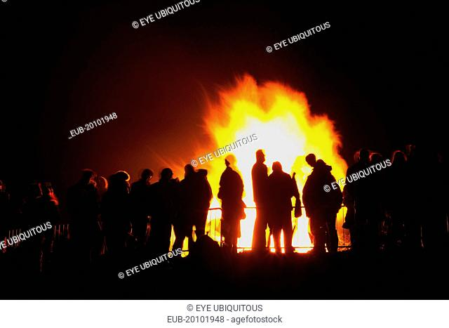 Festivals Guy Fawkes Bonfire People silhouetted by flames from fire on the beach