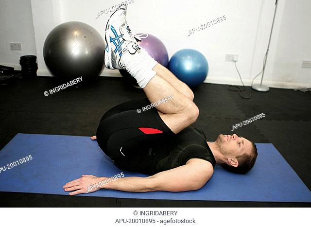 Man working out on mat in gym setting